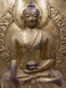 A LARGE GILDED COPPER REPOUSSE PANEL OF BUDDHA SEATED WITH HALO AND ENCIRCLED IN FIERY RING.