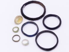 FOUR EGYPTIAN GLASS BANGLE BRACELETS, TWO GLASS RINGS, A GLASS RING FRAGMENT AND BRONZE RING (8)
