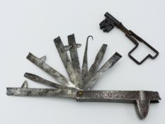 AN 18TH CENTURY WROUGHT IRON FOLDING FLEEM WITH EIGHT VARIOUS BLADES, HOOKS AND CUTTERS, THE OUTER