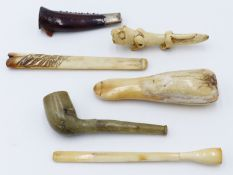 A CARVED GREEN HARDSTONE TOBACCO PIPE, THREE BONE CHEROOT HOLDERS, A SILVER MOUNTED LOBSTER CLAW