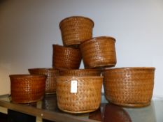A GROUP OF EIGHT SIMILAR WOVEN TRIBAL BASKETS.