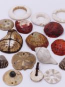 THREE TRIBAL SHELL BANGLES , FOUR RED CLAMSHEL PENDANTS, A SAND DOLLAR PENDANT, A COPPER MOUNTED