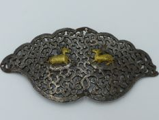 AN INDO PERSIAN STEEL AND SILVER GILT DAMASCENE BUCKLE COVER OR ORNAMENT OF PIERCED FOLIATE FORM