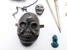 THREE SOUTH AMERICAN SILVER METAL SKULL MOUNTS, TWO GARMENT PINS AND EIGHT SMALL STONE EFFIGY