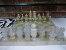 A CARVED ALABASTER CHESS SET OF TRADITIONAL FORM WITH GREEN/BROWN STRIATED AND OPAQUE WHITE PIECES