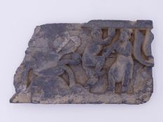 A CARVED GREY STONE SCHIST FRIEZE FRAGMENT DEPICTING MUSICIAN FIGURE AND DANCER ? TO THE SIDE OF