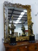 A LARGE VICTORIAN GILT ROCOCO STYLE FRAME WITH LATER SILVERED HIGHLIGHTS, NOW WITH A MIRROR PLATE.