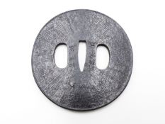 A 17TH CENTURY IRON TSUBA DECORATED WITH RADIATING INCISIONS AFTER A SUNBURST, A NOTE PERTAINING