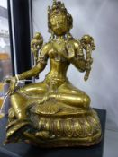 AN EASTERN POLISHED BRONZE AND COPPER FIGURE OF A SEATED DEITY ON A LOTUS FORM BASE. 18CM HIGH