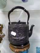 A JAPANESE MEIJI PERIOD IRON TEA KETTLE WITH LANDSCAPE RELIEF DECORATION, THE COPPER LID WITH