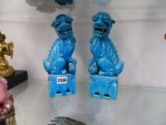 A PAIR OF CHINESE TURQUOISE GLAZED TEMPLE DOGS ON PIERCED RECTANGULAR BASES. 25CM HIGH X 9CM WIDE