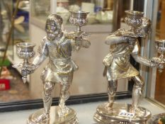 A PAIR OF SILVER PLATED TALL CANDLESTICKS MODELLED IN THE FORM OF TWO BEARDED MERCHANTS CARRYING
