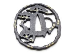 AN EDO PERIOD PIERCED IRON TSUBA, DECORATED WITH STYLIZED PINE TREES AND HIGHLIGHTED IN GILT.