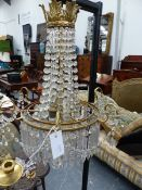 A REGENCY STYLE BRASS BASKET FORM CHANDELIER HUNG WITH PRISMS AND SWAGS