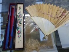 A CHINESE IVORY AND SILK FAN WITH CARVED EXTERIOR SCENES AND EMBROIDERED EXOTIC CRANE DESIGNS. IN