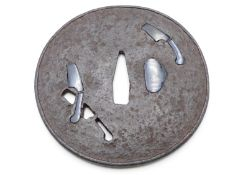 A LARGE CIRCULAR IRON TSUBA, PIERCED WITH THE PROFILE OF THREE CLEAVERS, TWO PLUGGED WITH SHAKUDO
