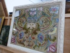 AN ANTIQUE SILKWORK PANEL OF FLOWERS AND BIRDS CENTERING A MASK. MOUNTED IN A CARVED AND LATER