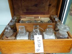 A LATE VICTORIAN OAK CASED APOTHECARY CASE WITH FITTED BOTTLES.