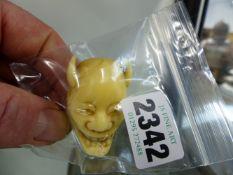 A JAPANESE CARVED IVORY DEVIL HANNIYA OKIMONO SIGNED. 4.2cms HIGH