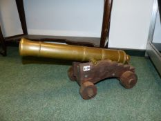 AN ANTIQUE BRONZE CANON ON WOODEN STEPPED CARRIAGE.