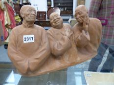 AN EARLY 20TH CENTURY TERRACOTTA FIGURE GROUP DEPICTING LES TROIS CHINOIS BY GASTON HAUCHECORNE.