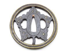 A PIERCED IRON TSUBA, DECORATED WITH A HEALING LEAF AND HIGHLIGHTED IN GILT WITH DEW DROPS AND