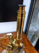 A LARGE LACQUERED BRASS MICROSCOPE BY ROSS, LONDON DISPLAYED UNDER A GLASS DOME.