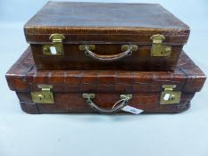 A LARGE CROCODILE SKIN SUITCASE WITH BRASS LOCKS TOGETHER WITH A SIMILAR SMALLER SILK LINED DRESSING