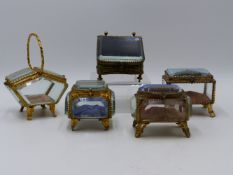 A SELECTION OF FIVE GLASS AND GILT METAL JEWELLERY CASKETS. (SMALLEST ONE BEING APPROX 6 CMS WIDE).