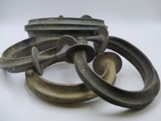 AN IMPRESSIVE GROUP OF FOUR VERY LARGE AFRICAN BRONZE TORQUE CURRENCY RINGS, PROBABLY YORUBA PEOPLE.