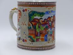 A CHINESE EXPORT LARGE FAMILLE ROSE MUG WITH PANELS OF DECORATION AND DRAGON FORM HANDLE. HEIGHT