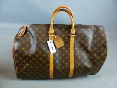 A LEATHER ZIP TOP DUFFEL BAG DECORATED WITH LV MONOGRAM. ZIP LENGTH APPROX 53 CMS.. TOGETHER WITH