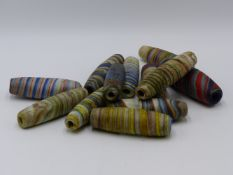 A GROUP OF TWELVE MULTI COLOURED LARGE GLASS TRADE BEADS (19TH CENTURY)