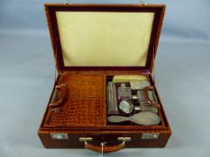 AN EARLY 20TH CENTURY CROCODILE LEATHER TRAVELLING VANITY CASE. PART FITTED WITH VARIOUS WHITE METAL