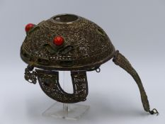 A TIBETAN SILVER (WHITE METAL) PIERCED AND FILIGREE. CORAL INSET, DECORATED HEAD DRESS OR HELMET,