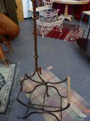 A WROUGHT IRON STANDARD LAMP TOGETHER WITH AN UNUSUAL WROUGHT IRON FOLDING STOOL.