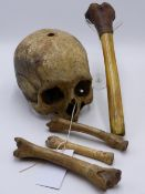 AN EARLY SPECIMEN HUMAN SKUL TOGETHER WITH FOUR TRIBAL CARVED BONES INCLUDING A LEATHER WRAPPED