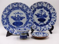 TWO SIMILAR CHINESE EXPORT BLUE AND WHITE PLATES EACH WITH A CENTRAL MEDALLION OF A BASKET OF