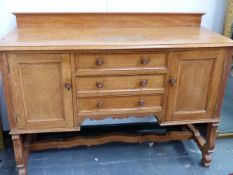 A HEAL'S OAK SMALL SIDEBOARD WITH THREE DRAWERS FLANKED BY CUPBOARDS. 136CMS.WIDE.