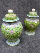 TWO SIMILAR CHINESE FAMILLE ROSE BALUSTER VASES WITH A PAIR OF ASSOCIATED DOME FORM COVERS.
