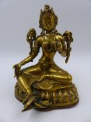 A TIBETAN GILT BRONZE AND COPPER FIGURE OF A SEATED DEITY. H.18cms.