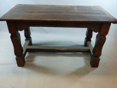 A CARVED OAK SMALL REFECTORY TABLE, PLANK TOP WITH BREADBOARD ENDS AND SQUARED LEGS JOINED BY MEDIAL