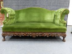 A CARVED WALNUT CAMEL BACK SETTEE IN THE IRISH GEORGIAN TASTE WITH BUTTONED ROLL OVER ARMS,