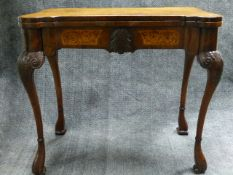 AN ANTIQUE AND LATER CARVED AND INLAID WALNUT EARLY GEORGIAN STYLE GAMES TABLE WITH SHAPED TOP AND
