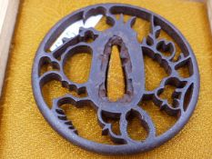 A 17th.C. PIERCED IRON TSUBA DECORATED AFTER STYLIZED BIRDS WITHIN A PLUM TREE