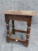 AN EARLY OAK JOINT STOOL WITH CARVED FRIEZE. W.46cms.
