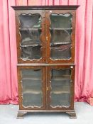 A 19th.C.WALNUT TWO PART DISPLAY CABINET WITH FOUR SHAPED PANEL GLAZED DOORS ENCLOSING SHELVES. W.