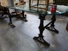 AN IRON TRESTLE BASED GLASS TOP TABLE.