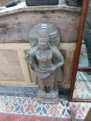 A LARGE EASTERN CARVED SANDSTONE FIGURE OF A STANDING DEITY.