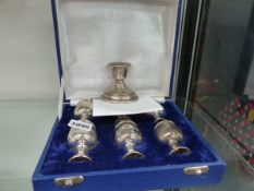 A SILVER CANDLESTICK TOGETHER WITH WHITE METAL EGG CUPS